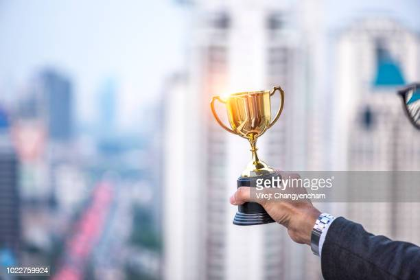 hand of businessman president holding gold trophy, business winner award - millionnaire stock photos and pictures
