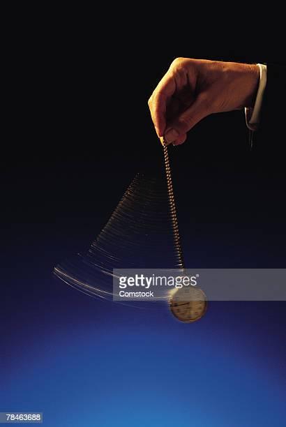 Hand of businessman swinging a pocket watch