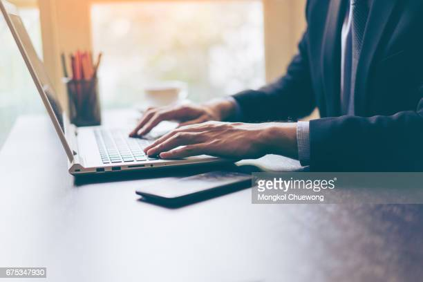 Hand of businessman using his laptop with a cup of coffee on office desk. Portrait of business man using laptop in office.