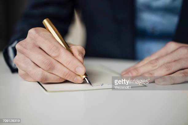 Hand of businessman writing with golden fountain pen, close-up