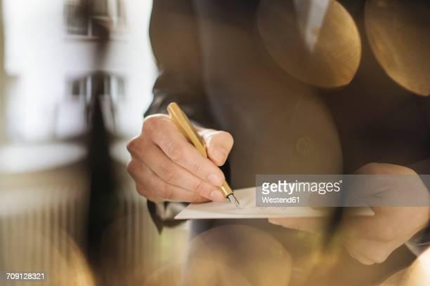 hand of businessman writing with golden fountain pen on notepad - reichtum stock-fotos und bilder