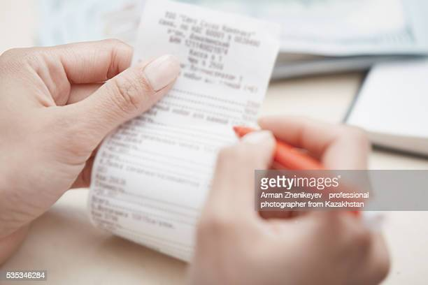 Hand of businesswoman checking invoice