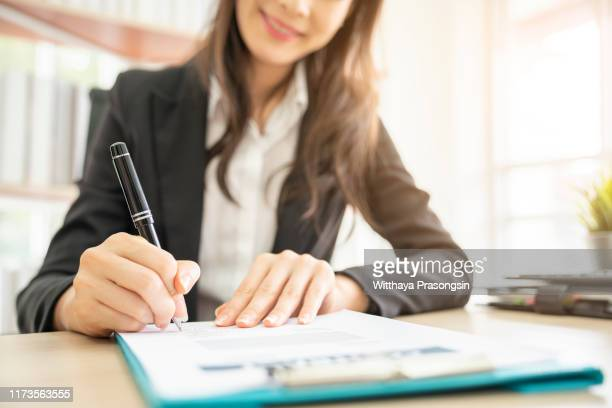 hand of businesswoman writing on paper in office - ballpoint pen stock pictures, royalty-free photos & images