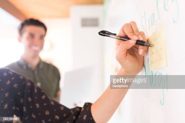 hand of businesswoman writing on whiteboard adhesive notes - heshphoto stock pictures, royalty-free photos & images