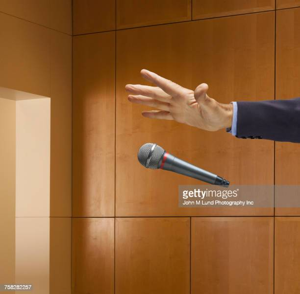Hand of Caucasian businessman dropping microphone in office