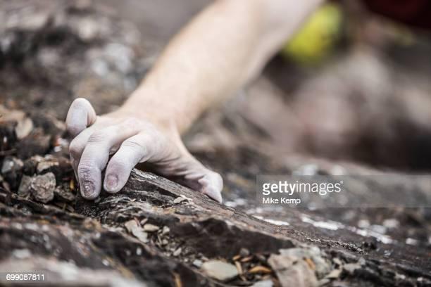 Hand of Caucasian man rock climbing