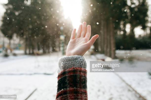 Hand of Caucasian woman catching falling snow