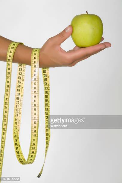 Hand of Caucasian woman holding green apple and measuring tape