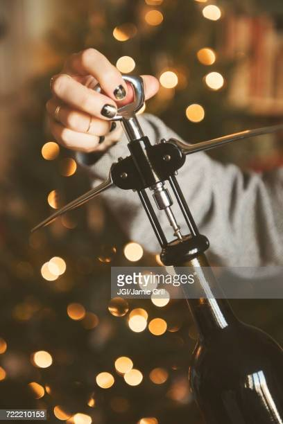 Hand of Caucasian woman opening wine bottle with corkscrew
