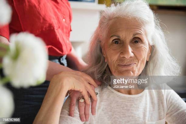 hand of daughter on shoulder of older mother - daughter photos stock photos and pictures