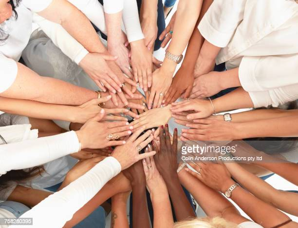 hand of diverse women huddling - mid section stock photos and pictures