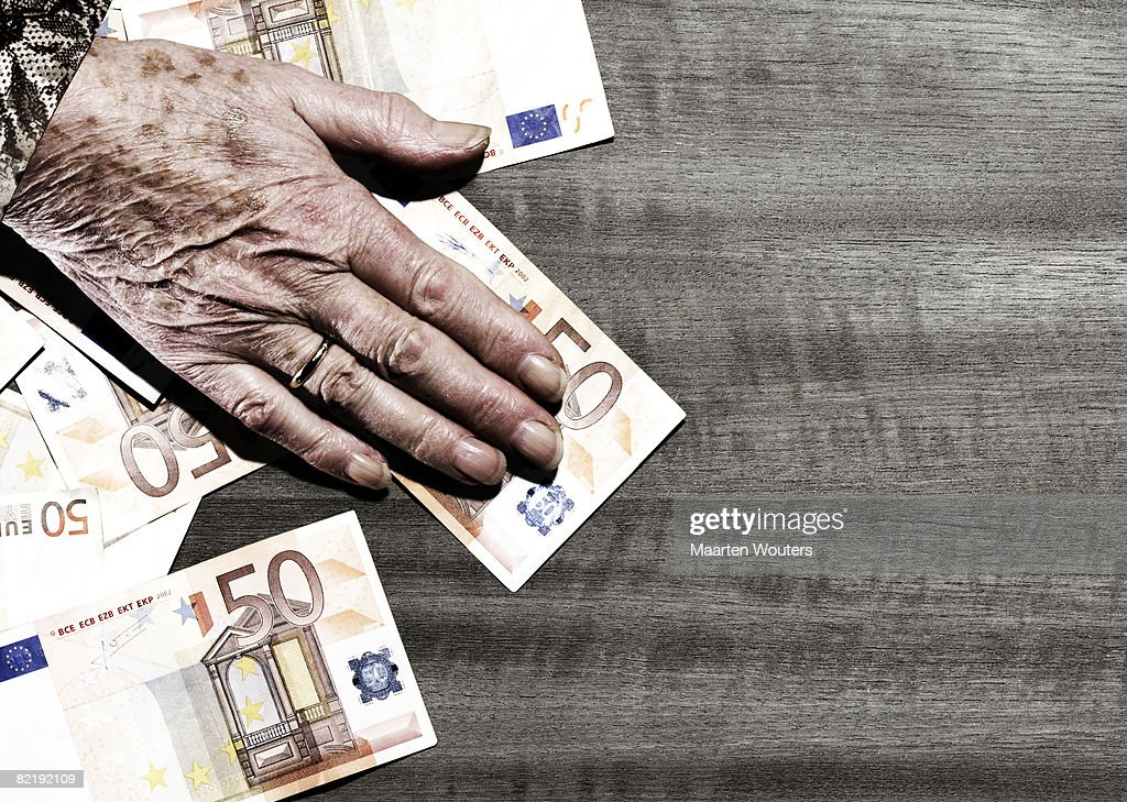 Hand of elderly woman on table with euro  : Stock Photo