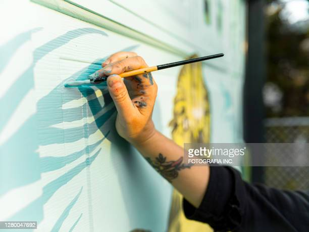 hand of female mural artist at work - mural stock pictures, royalty-free photos & images