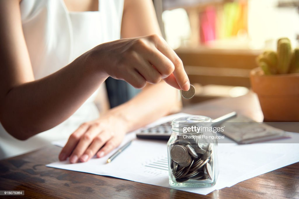 Hand of female putting coin in jar with money stack step growing growth saving money, Concept finance business investment : Stock Photo
