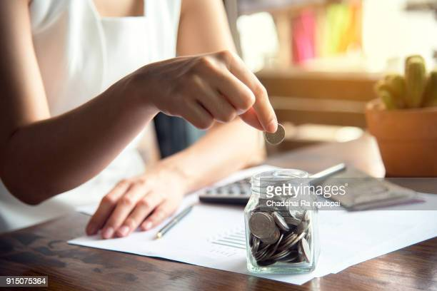 hand of female putting coin in jar with money stack step growing growth saving money, concept finance business investment - savings stock pictures, royalty-free photos & images