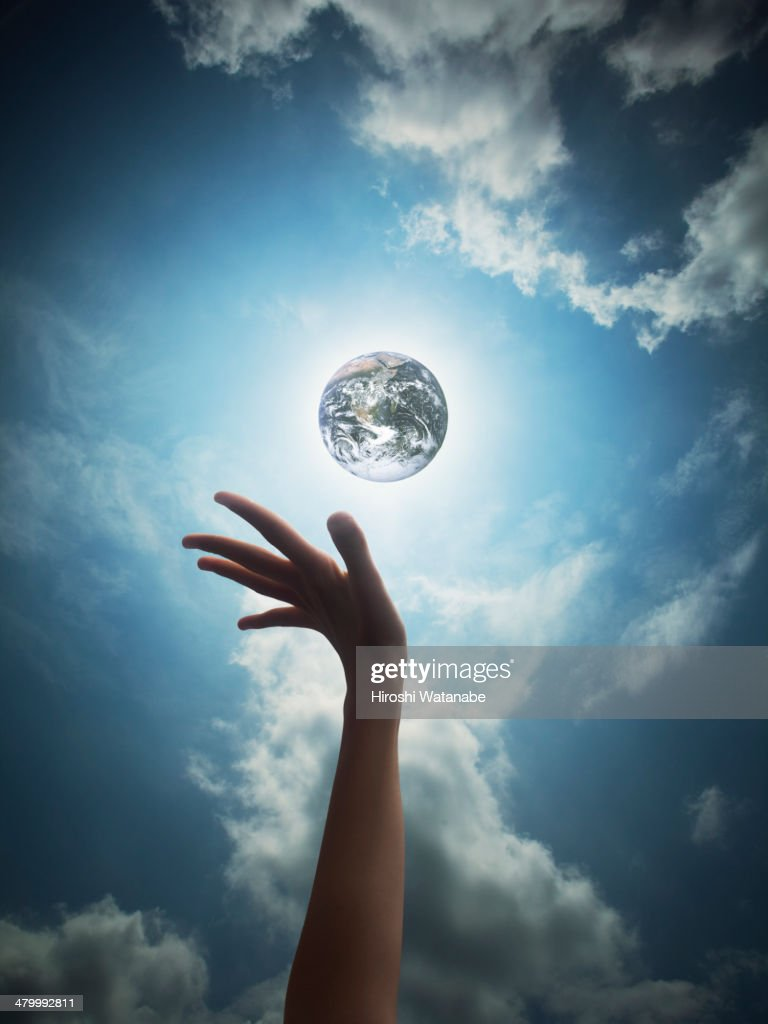 Hand of girl seems to reach to the Earth in the sk : Stockfoto