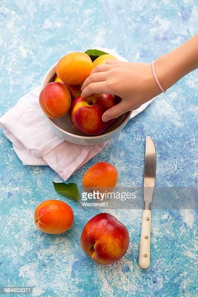 Hand of girl taking nectarine