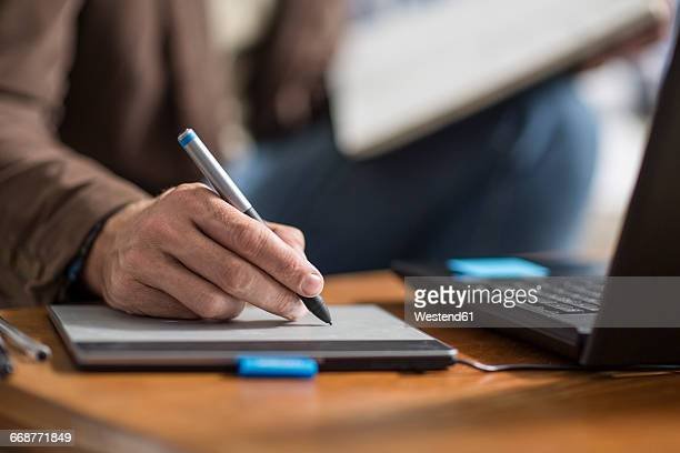 Hand of graphic designer, graphics tablet and pencil
