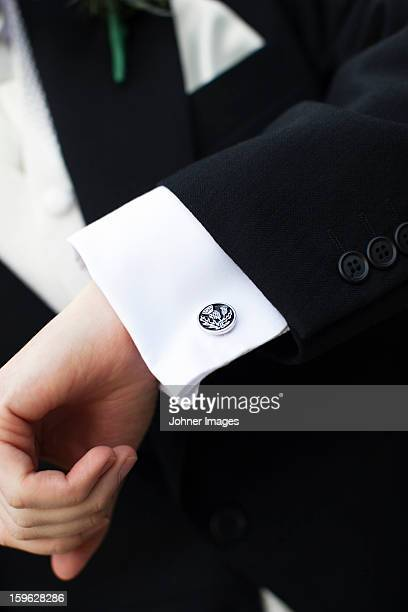 Hand of groom wearing suit and shirt with cuff pins