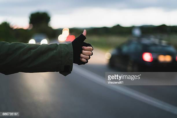 hand of hitchhiking young woman waiting at roadside in the evening - hitchhiking stock pictures, royalty-free photos & images