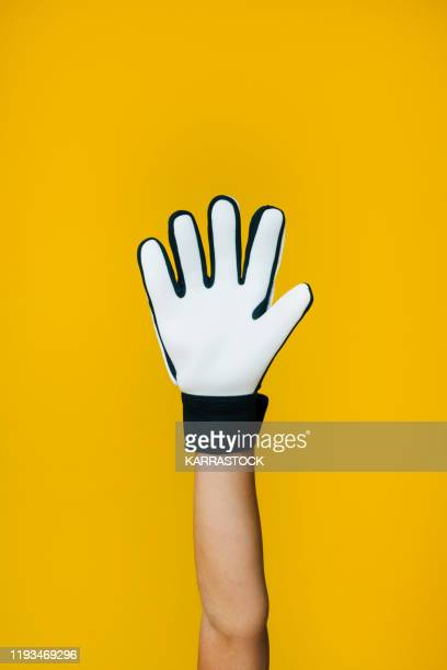 hand of little boy with soccer goalkeeper gloves on yellow background - sports glove stock pictures, royalty-free photos & images