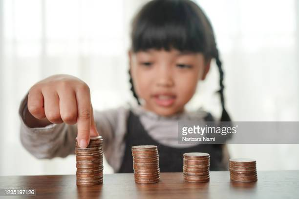 hand of little child girl putting coins to stack of coin step growing growth saving money, concept finance business investment, and kid saving money for future education. - stability stock pictures, royalty-free photos & images
