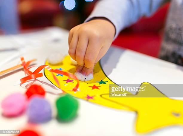 hand of little girl tinkering christmas decoration, close-up - stella cometa foto e immagini stock