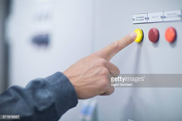 hand of male technician pressing yellow button on control panel - push button stock pictures, royalty-free photos & images