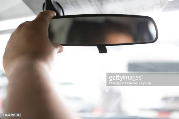 Hand Of Man Adjusting Rear-View Mirror In Car