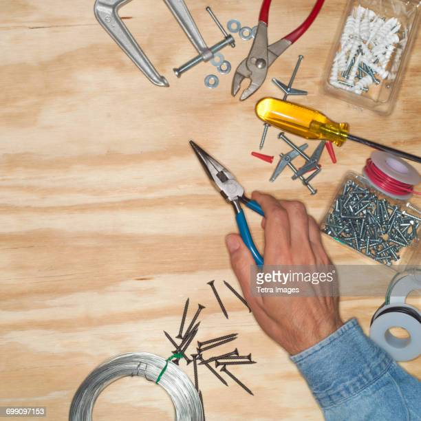 Hand of man holding pliers in workshop