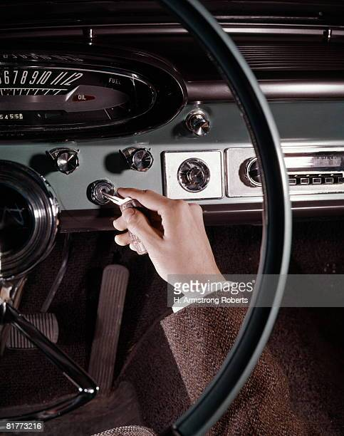 Hand Of Man Inserting Key Into Automobile Ignition Close-Up Detail Interior Car.