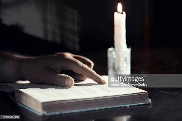 hand of man reading book at candle's light - science photo library stock pictures, royalty-free photos & images