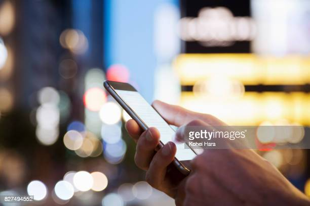 hand of man using a smart phone on the urban street at night - 可動性 ストックフォトと画像
