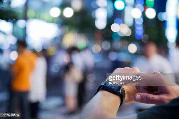 Hand of man using a smart watch on the urban road at night