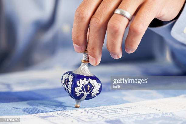 hand of man with dreidl - dreidel stock photos and pictures