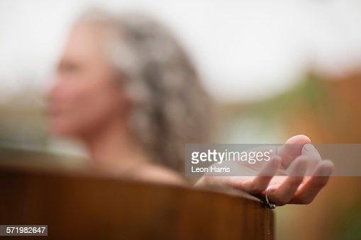 Hand Of Mature Woman Meditating In Hot Tub At Eco Retreat