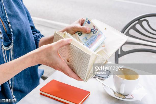 hand of mature woman removing euro note from purse at sidewalk cafe, fiesole, tuscany, italy - money stock photos and pictures