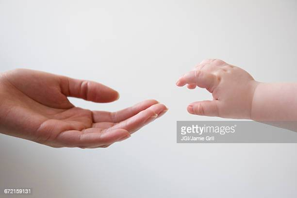 Hand of mother reaching for hand of baby son