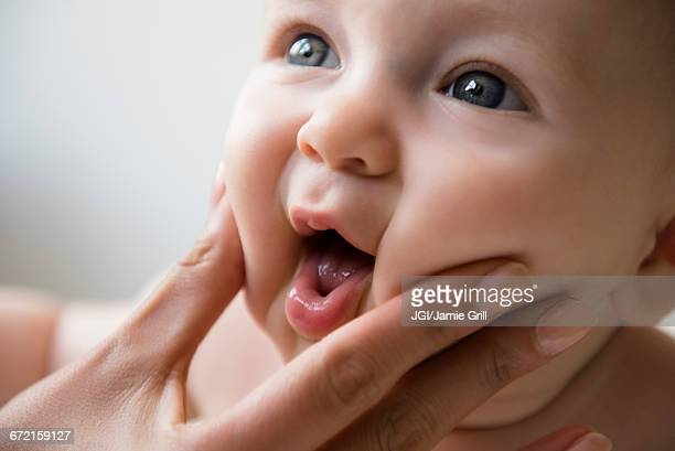 hand of mother squeezing cheeks of baby son - cheek stock pictures, royalty-free photos & images