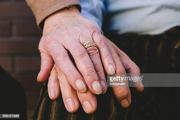Hand of old woman on husbands hand