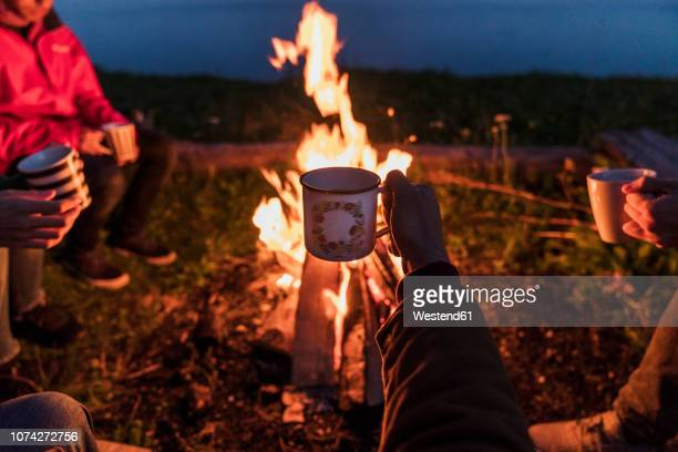 hand of person holding tea cup, group of people sitting at a camp fire - hygge stock pictures, royalty-free photos & images