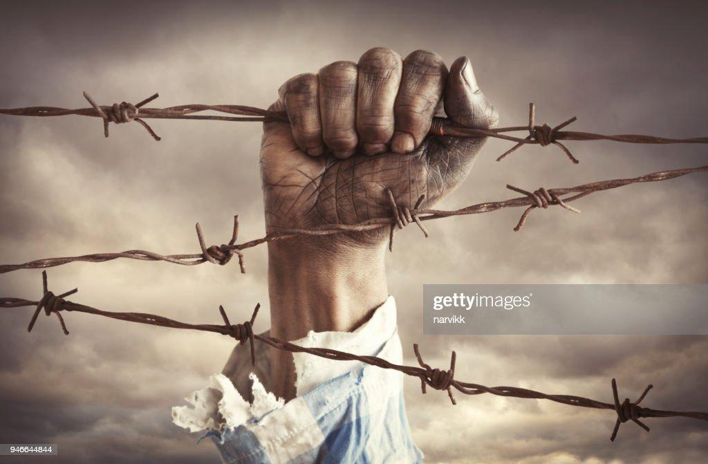 有刺鉄線を保持している難民の手 : ストックフォト