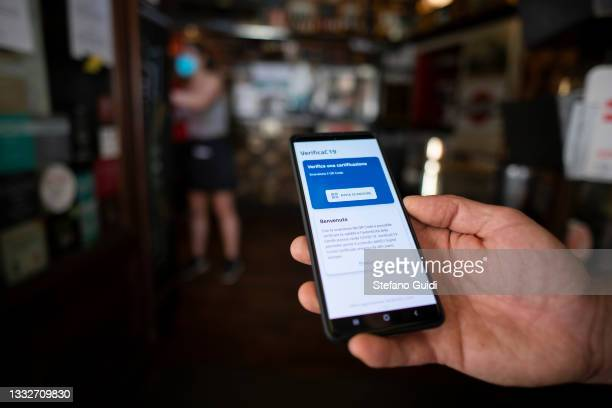 Hand of restaurateur shows his smartphone with the ready-to-use green pass reader application on August 6, 2021 in Turin, Italy. The Italian...