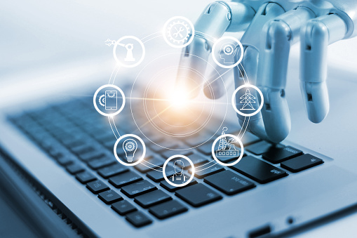 Hand of robotics connecting to industrial network connection on laptop. Artificial intelligence. Futuristic technology and manufacturing concept. 1022892524