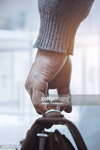 Hand of senior man holding luggage at departure area