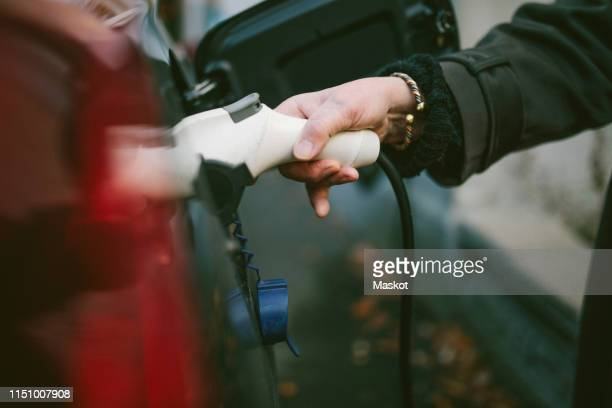 hand of senior woman charging electric car - elektroauto stock-fotos und bilder
