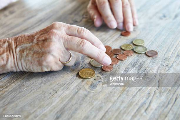 hand of senior woman counting coins, close-up - armoede stockfoto's en -beelden