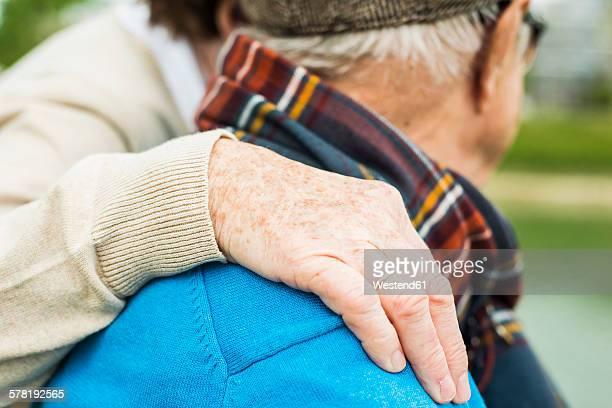 Hand of senior woman on shoulder of her husband
