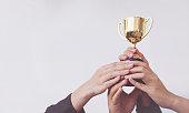 Hand of Team business holding a golden trophy, Concept Teamwork