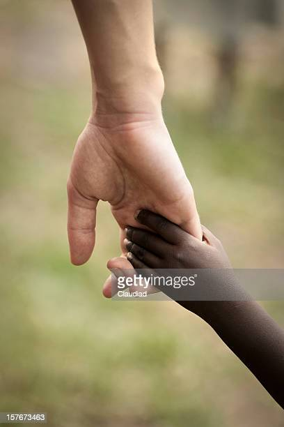 Hand of white adult and black child